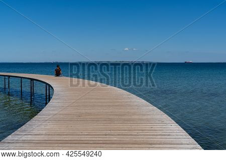 A Slim Woman Sits Alone On A Circular Boardwalk Leading Out And Over A Calm Blue Ocean