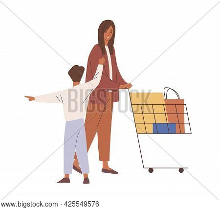 Mother And Child During Shopping. Woman And Kid Pushing Supermarket Cart Full Purchases In Bags And