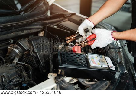 Close Up Hand Of Car Repairman With Multimeter Device For Check Up Car Battery Life, Battery Inspect