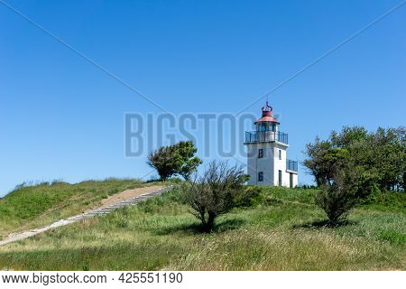 A View Of The Hundested Lighthouse On Ist Grassy Hill Under A Blue Sky