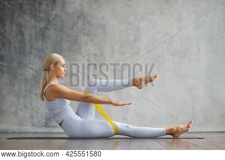 Young and sporty girl in sportswear is doing exercises in home interior using resistance band. Fit and slender blond woman goes in for sports and fitness. Healthcare, fat burn and wellness.