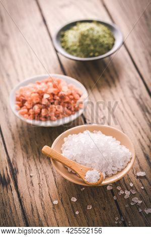 Assortment of salts in bowls : white rock salt, Himalayan salt and chives salt on wooden background