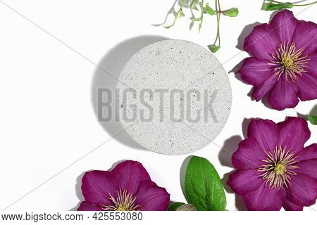 A Podium Made Of Concrete With Pink Clematis Flowers, For The Presentation Of Packaging And Cosmetic