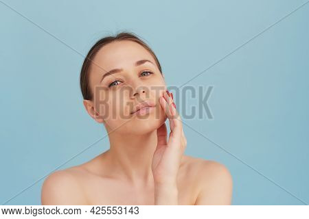 Beauty Portrait Of Woman With Clean Healthy Skin On Blue Background. Smiling Dreamy Beautiful Woman