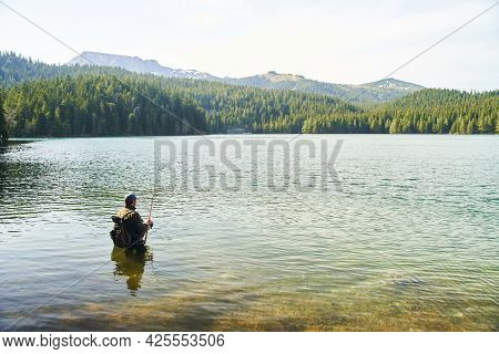 Fisher Man Stands In The Water And Catch Fish In The Lake On A Background Of Mountains