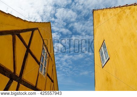 Nysted, Denmark - 11 June, 2021: Half-timbered Yellow Houses In Stark Contrast Under A Blue Sky With