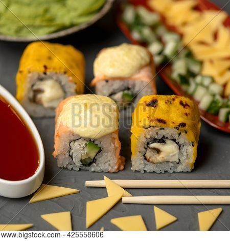 Hot Grilled Philadelphia Roll. Sushi Rolls Baked With Cheese. Chopsticks In Foreground. Closeup Shot