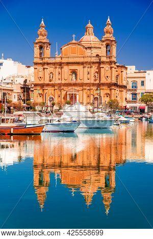 Valletta, Malta. Msida Marina Boat And St Joseph Church Reflection Into Water.