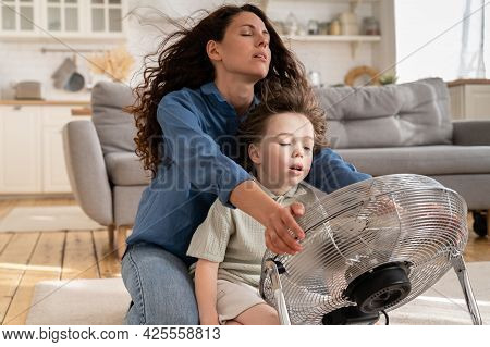 Happy Mom And Small Kid Refreshing Sit Near Big Indoor Ventilator Blowing Cooling Fresh Air At Home