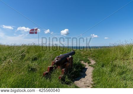 An Old Cannon And Danish Flag On The Coast Of Northern Denmark