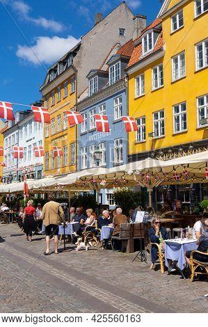 Copenhagen, Denmark - 13 June, 2021: People Enjoy A Summer Day In The Busy Nyhavn Quarter On The Wat