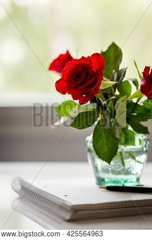 A Bouquet Of Red Roses In A Glass Transparent Vase. Notebook And Pen. Place For Your Text. Copy Spac