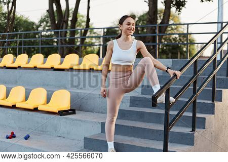 Portrait Of Female Coach With Dark Hair Stands On Stairs On The Stadium, Dressed In Sports Uniform,