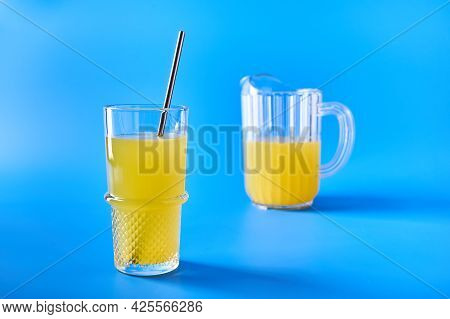 Orange Juice In Glass With Straw And In Glass Jug On Blue Background. Refreshing Summer Drink. Copy