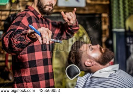 Men Barber Shaves His Beard. Bearded Male Sitting In An Armchair In A Barber Shop While Hairdresser