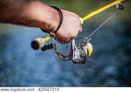 Fisherman Hand Holding Fishing Rod With Reel. Fishing Reel. Fishing Rod With Aluminum Body Spool. Fi