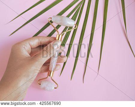 Female Hands Holding Rose Quartz Jade Face Roller. Pink Gua Sha Massage Tool On Pink Background. Fac