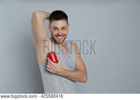 Handsome Man Applying Deodorant On Grey Background. Space For Text
