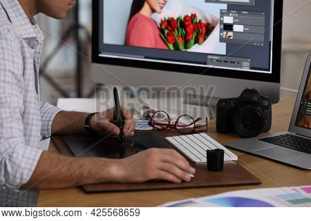 Professional Retoucher Working On Graphic Tablet At Table, Closeup