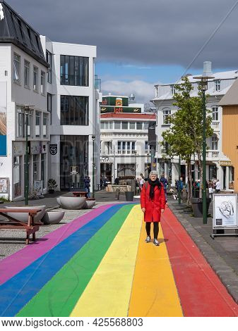 11 June 2021, Reykjavik Downtown, Iceland. A Woman In Red Coat, Walking Down The Rainbow Street, Sko