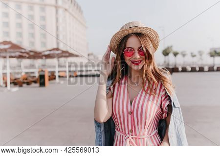 Outdoor Portrait Of Pleasant Stylish Girl In Vintage Hat Standing On City Background. Good-humoured