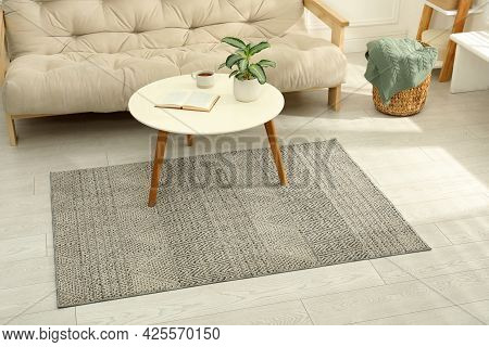 Stylish Rug With Pattern And Table On Floor In Living Room