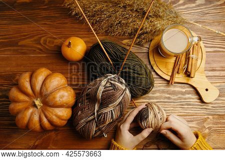 Hands In Orange Sweater With Yarn, Knitting Needles , Coffee And Cinnamon Sticks On Wooden Table. Cr