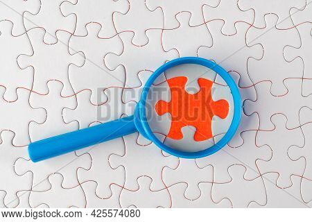 A Magnifying Glass On White Jigsaw Puzzle. Problem Analysis And Solving Concept
