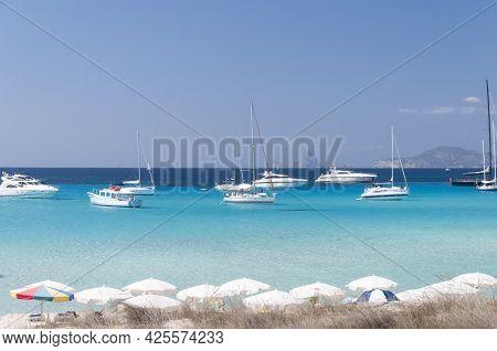 Luxury Boats Anchored Near A Beach In Formentera, Mediterranean Sea, Spain. On The Beach Open Umbrel