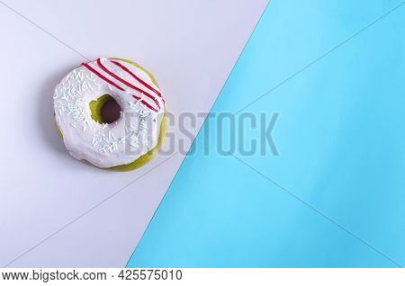 Donuts With Pink Icing On A Colored Background. Sweet Donut On A Two-color Divided Background Of Cop