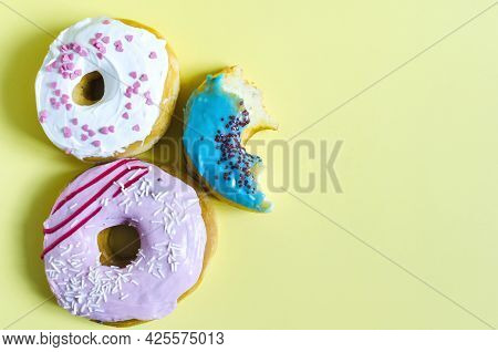 Donuts With Colored Glaze On A Bright Yellow Background. Sweet Donuts And A Bitten Donut On A Light