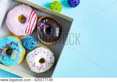 Fresh Donuts With Colored Glaze In A Cardboard Box. Sweet Donuts In A Box On A Light Background, The