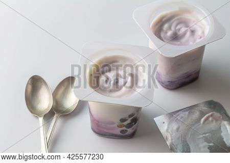 Blue Berry Yogurt Cups With Natural Yoghurt And Blue Berries - Two Cups And Two Spoons With Creamy F