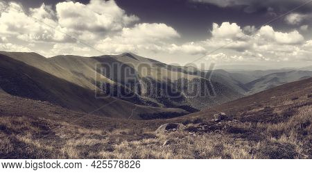 Panorama With Sunny Day On Top Of Green Carpathian Mountains Range With Dark Sky And Low Clouds On T