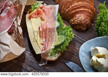 Croissant Sandwich With Jamon Meat Slices, Green Lettuce Leaves, Fresh Cucumbers, Cheese, Butter And