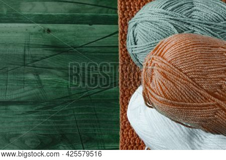 Skeins Of Colored Yarn On A Colored Wooden Background Top View Knitting Concept. Large Skeins Of Thr