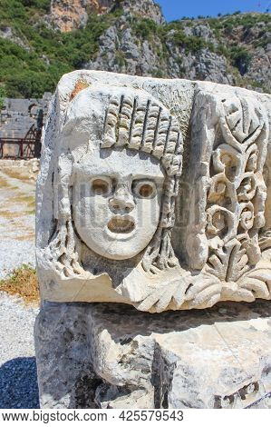 Masks And Rock Tombs In Myra, Turkey. Ancient Tomb By Lycia In Fethiye, Archeology And Travel Concep