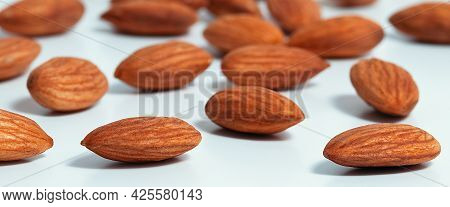 Background Of Almonds. Fried Almonds. Scattered Almond Grains. Background For Advertising