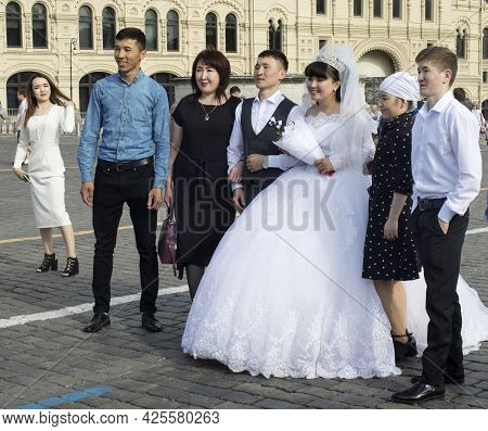 2020, People Are Photographed On Red Square Against The Background Of St. Basil's Cathedral. Asian W