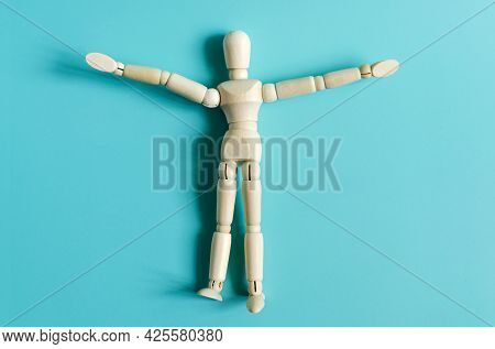 The Figure Of A Wooden Man In Close-up On A Colored Background. Figure Of A Wooden Man On A Light Ba