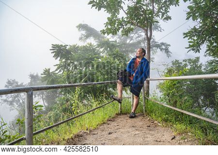 Asian Fat Guy On  Phu Thok Chiang Khan In Foggy Day.chiang Khan Is An Old Town And A Very Popular De