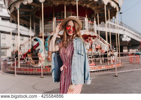 Good-humoured Female Model In Straw Hat Chilling During Photoshoot Near Carousel. Trendy Carefree Gi