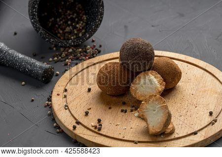 Spicy Cheese Covered With Round Type Spices On A Wooden Surface. Spices And Cheese