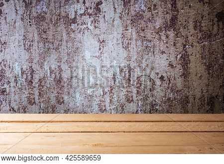 Wooden Table Made Of Boards Near An Old Shabby Wall