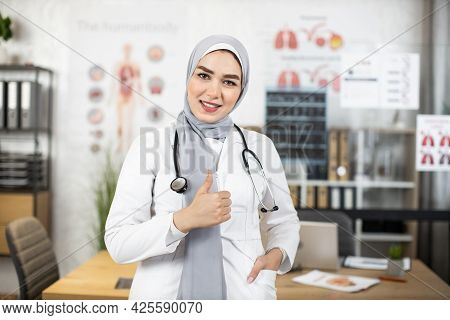 Arabian Health Care Worker Wearing Hijab And White Lab Coat Showing Thumb Up And Smiling On Camera.