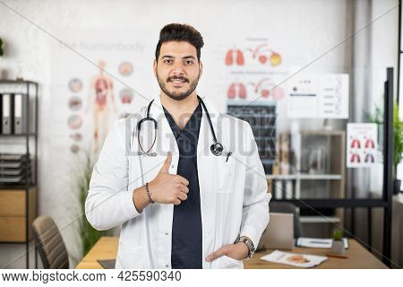 Competent Young Muslim Arabian Male Medical Worker In White Lab Coat Showing Thumb Up While Posing A