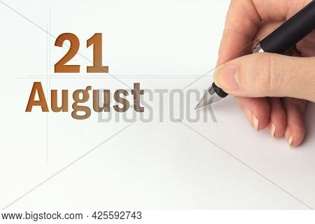 August 21st . Day 21 Of Month, Calendar Date. The Hand Holds A Black Pen And Writes The Calendar Dat