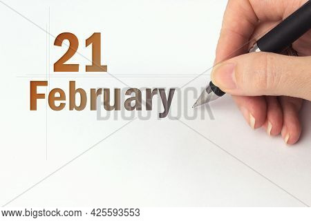 February 21st . Day 21 Of Month, Calendar Date. The Hand Holds A Black Pen And Writes The Calendar D