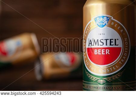 Beer Cans. Amstel Beer In Cans Close-up. World Famous Dutch Brand. Blurred Wood Background. Selectiv