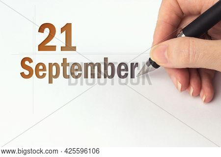 September 21st . Day 21 Of Month, Calendar Date. The Hand Holds A Black Pen And Writes The Calendar